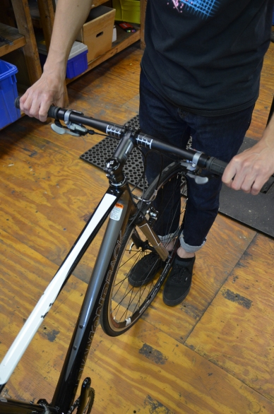Pull the brake levers, brace the front wheel between your legs, and pull on the handlebars. Check to see if the steerer tube rocks inside of the headtube
